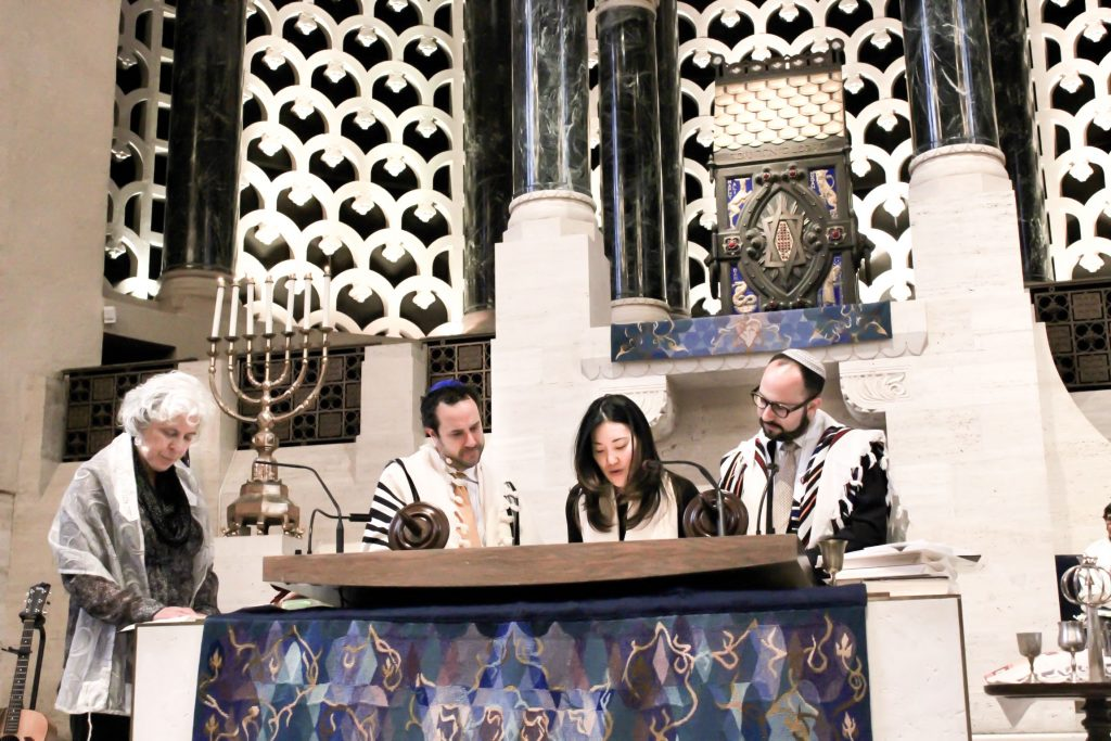 With the support of a rabbi and two cantors, reading from Torah