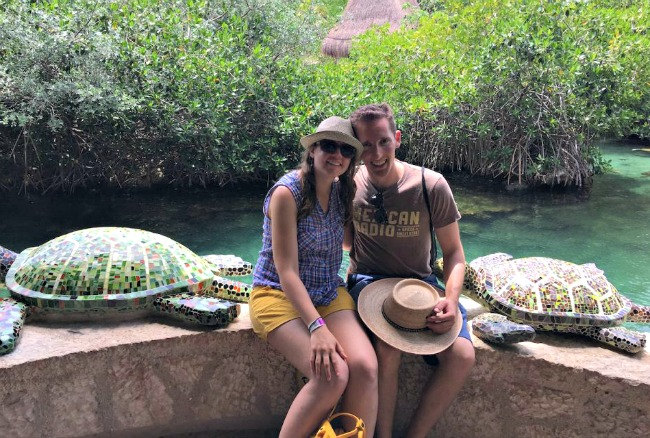 Laura and Zach sitting on a wall with mosaic turtles on either side in the Caribbean and relieving some stress.