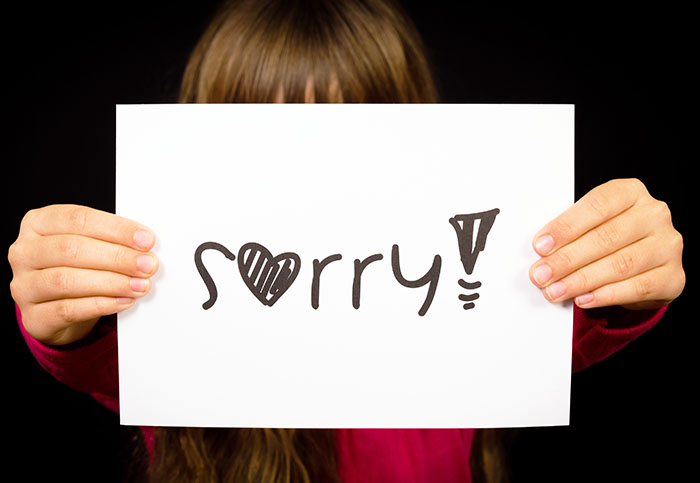 Child Holding Sign That Says Sorry