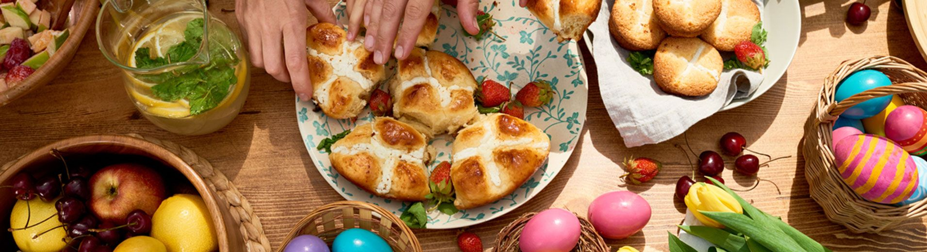 Table full of food and easter eggings with hands taking bread