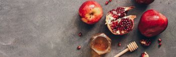 Cut fresh pomegranates and seeds on a table alongside apples and a honey jar.