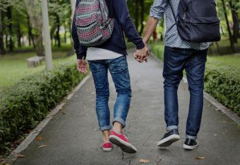 Couple walking hand in hand outdoors.