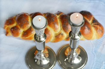 Two candles next to a challah bread.
