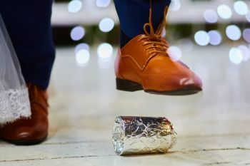 image of a foot at a wedding stepping on a glass wrapped in aluminum foil.