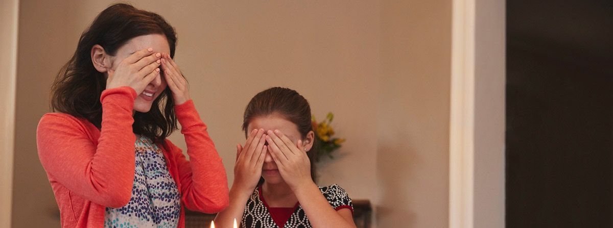 Woman and young girl covering their eyes.