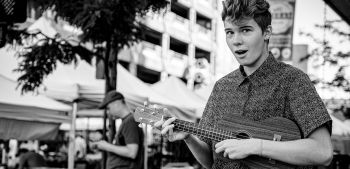Young man singing play a ukulele outside