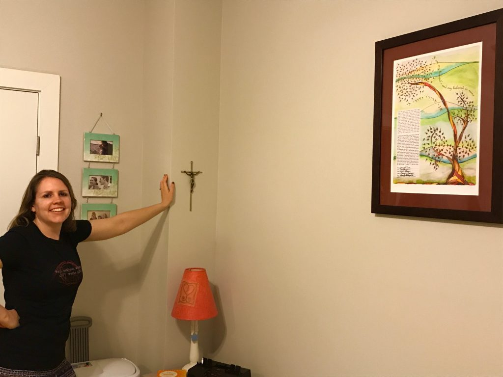 young woman leans against wall in bedroom, with family photos, ketubah and crucifix hanging on the wall