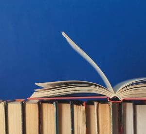 A series of books lined up on their spines and another book open laying on top of them, all against a bright blue background.