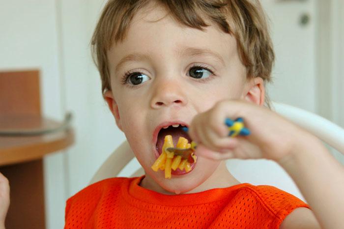 Boy eating mac_cheese