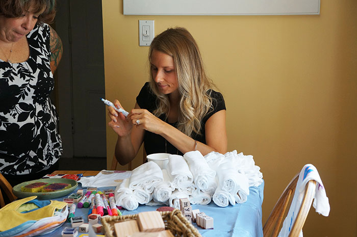 Marketing director Liz (left) and executive assistant Jamie make my baby beautiful onesies and bibs at my baby shower.