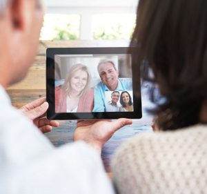 Shot of a married couple video calling their loved ones using their digital tablet