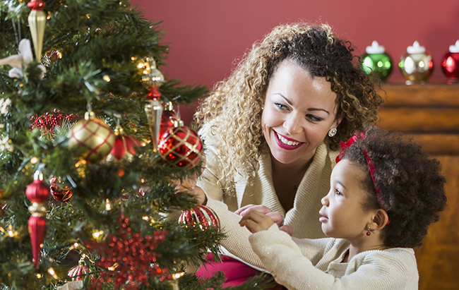 Mother helping little girl decorate Christmas tree