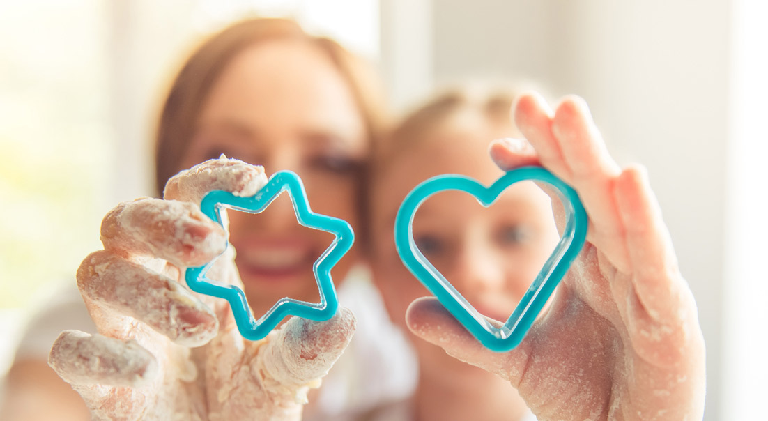 Two girls holding turquoise holiday cookie cutters with hands covered in dough.
