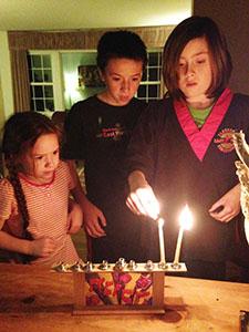 Lela's kids light the menorah