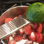 frozen strawberries in mixing bowl with grated lime