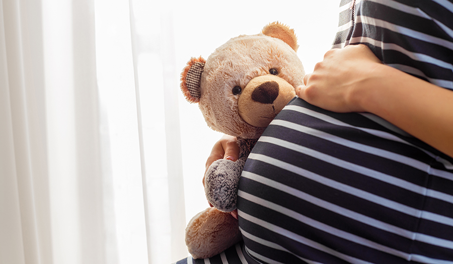 Pregnant woman's belly with a teddy bear on it.