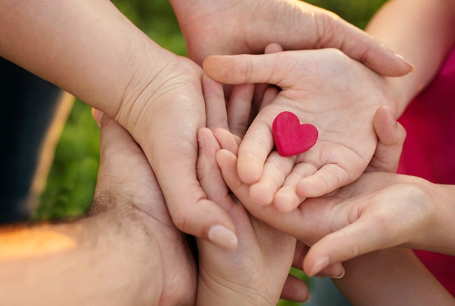 Family holds red heart in hands