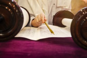 A hand following words from the Torah with a pen.