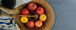 A basket of apples next to some fabric on a table.