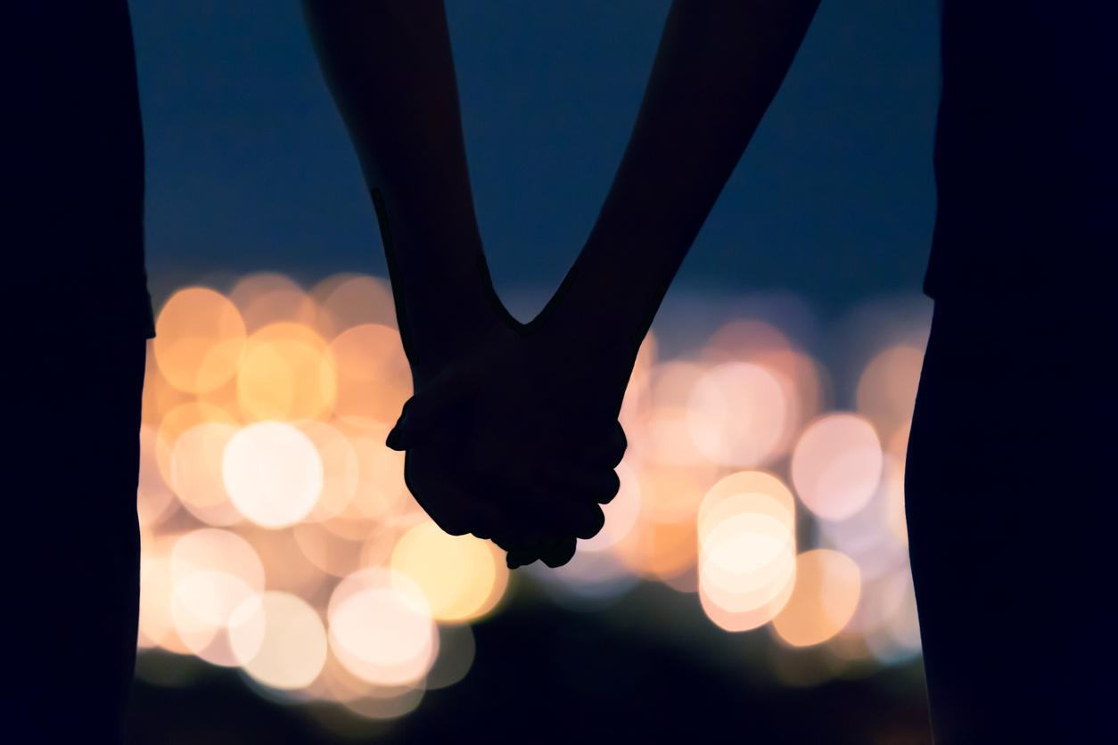 Sunset silhouette of handing hands.