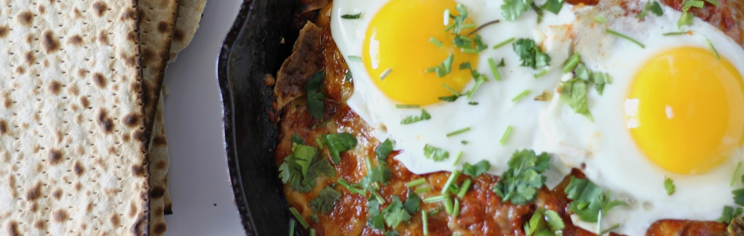 A pan with chila, a tomato based dish topped with an egg over easy.