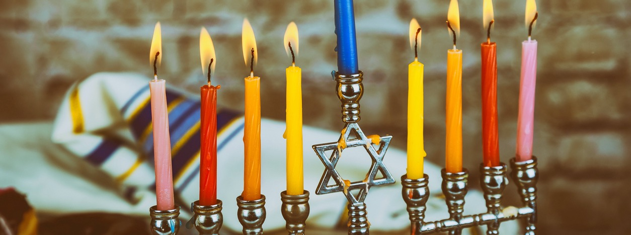 A menorah with a rainbow of brightly colored candles all lit.