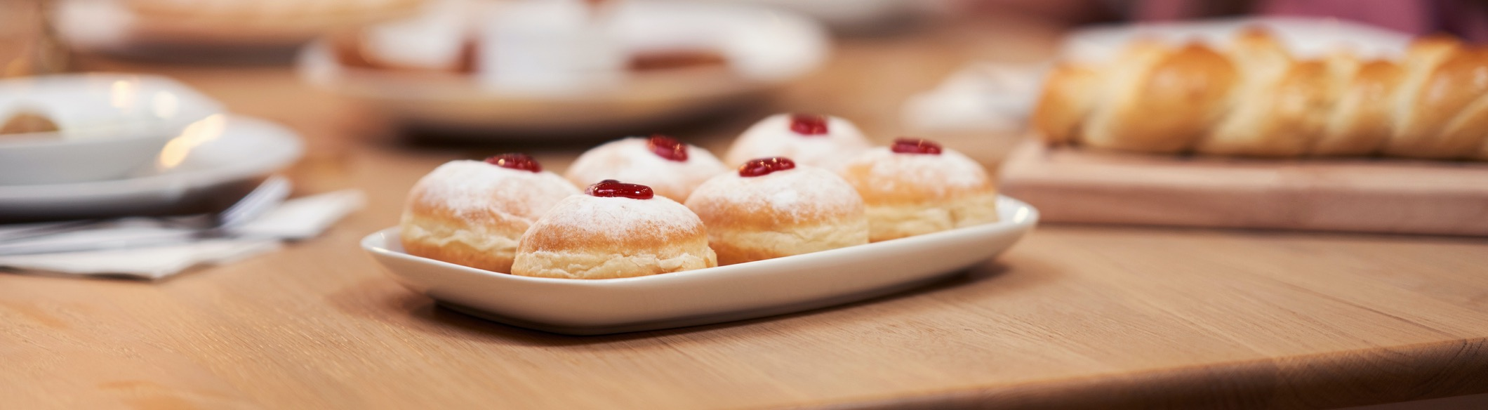A plate of donuts with a cherry on top.