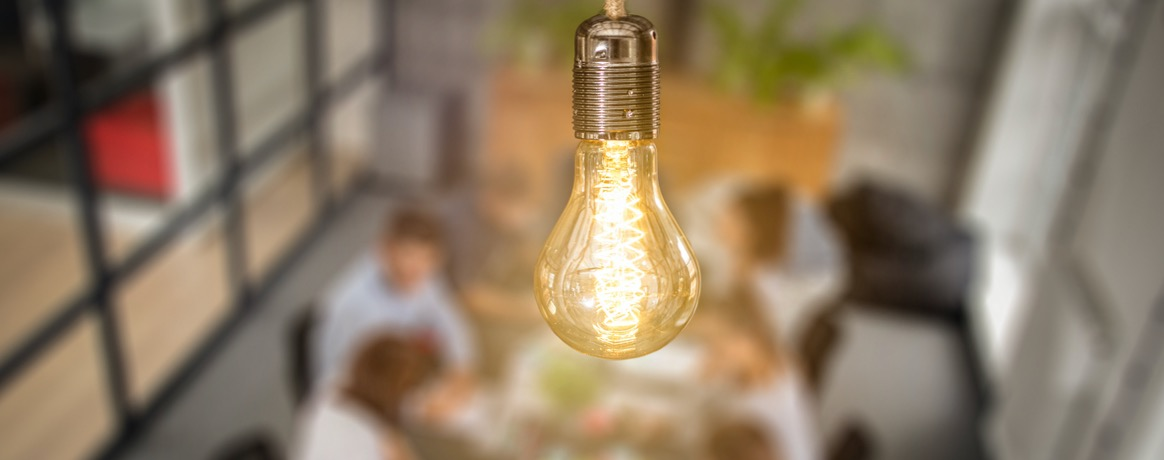 Image of a lit lightbulb in the foreground and a blurred out background of people sitting at a table.