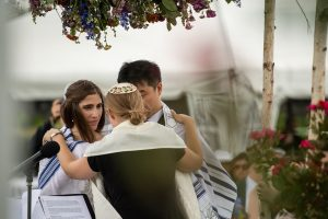 A jewish officiant with her arms around a bride and groom.