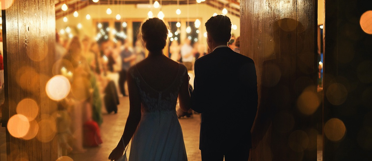 Silhouette image from the back of a bride and groom walking into a reception room.
