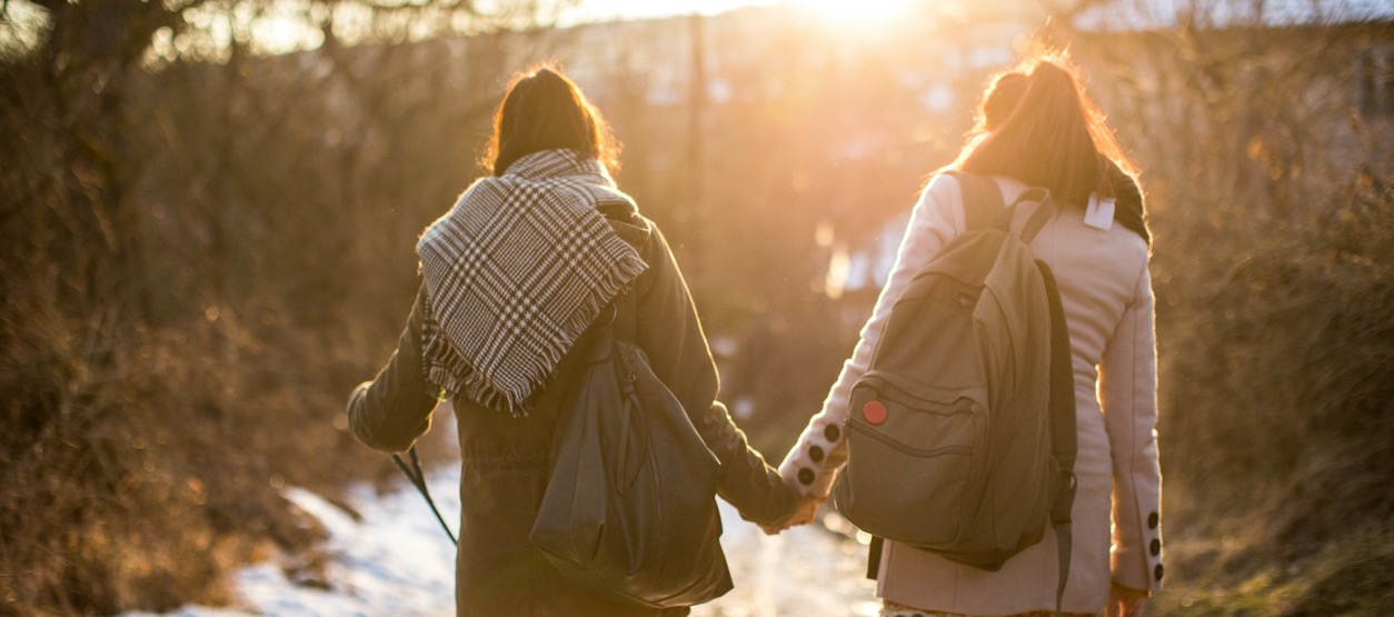 Two women walking outdoors holding hands.