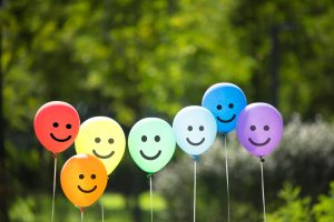 A rainbow of colored balloons with a smiley face written on them outdoors against a backdrop of greenery.